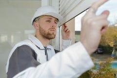Appaltatore che esamina l'otturatore del rullo della finestra fotografie stock libere da diritti