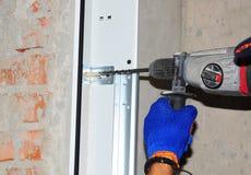 Appaltatore che installa la porta del garage Cacciavite automatico di uso del riparatore per perforare la parete per l'installazi fotografia stock