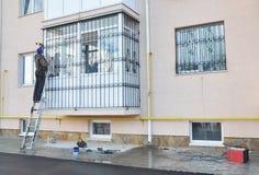 Appaltatore che installa le barre di sicurezza del ferro della finestra del balcone Barre di sicurezza per le finestre ed il balc Fotografia Stock
