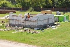 Appaltatori che costruiscono nuova casa moderna dai blocchi in calcestruzzo aerati fotografia stock