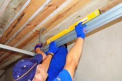 Appaltatori che installano l'apri della porta del garage della casa e che sollevano sistema fotografia stock