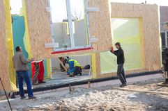 Appaltatori che installano la casa delle pareti del pannello del bordo del compensato della struttura modulare sul cantiere domes fotografia stock libera da diritti
