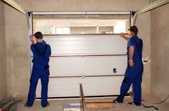 Appaltatori che installano, riparazione, porta d'isolamento del garage Sigillo alla porta del garage, sostituzione della porta de fotografie stock