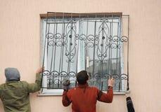 Appaltatori del costruttore che installano le barre di sicurezza del ferro della finestra per protezione fotografia stock
