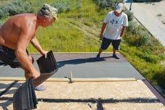 Appaltatori del Roofer che pongono e che installano le assicelle dell'asfalto Coprendo costruzione con il tetto immagini stock libere da diritti