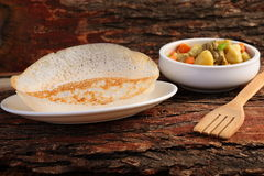 Appam served with hearty mutton stew. Kerala cuisine-Soft Appam served with hearty mutton stew on a wooden background Royalty Free Stock Photos