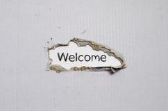 Apparaître bienvenu de mot derrière le papier déchiré Image libre de droits