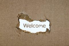 Apparaître bienvenu de mot derrière le papier déchiré Photo libre de droits
