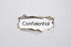 Apparaître confidentiel de mot derrière le papier déchiré images libres de droits