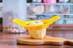 Apparaat om appel in plakken en een appel op de keukenlijst te snijden stock fotografie
