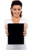 Apparat för kvinnaholdingtablet, uppvisning det till kameran Arkivfoto