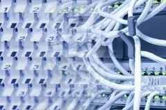 Apparater för elektroniska kommunikationer: strömbrytare, routers, förbindande kablar och kontaktdon, lapppaneler arkivbild