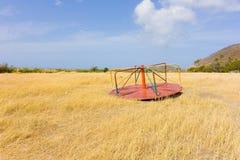 Apparecchiatura scartata del campo da giuoco in un campo invaso su Bequia fotografia stock