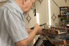 Appareil électronique fonctionnant de vieil homme utilisant des pinces Images libres de droits