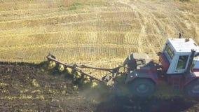 Appareil de photographie aérienne semblant le bas droit anding avec un tracteur plantant des pommes de terre dans un domaine banque de vidéos