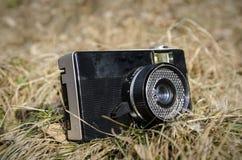 Appareil-photo analogue de photo de vieux vintage à l'arrière-plan d'herbe de nature Photographie stock libre de droits
