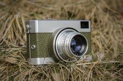 Appareil-photo analogue de photo de vieux vintage à l'arrière-plan d'herbe de nature Photos stock