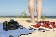 Appareil-photo avec la lentille se trouvant une serviette sur le sable à la plage Image libre de droits