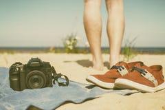 Appareil-photo avec la lentille se trouvant une serviette sur le sable à la plage Photos libres de droits