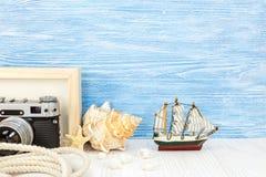 Appareil-photo classique avec le cadre, les coquillages et le bateau vides de photo sur bleu Photo libre de droits