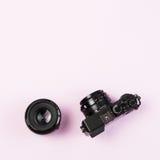 Appareil-photo compact numérique de vintage et lentille 50mm de difficulté sur le pastel rose Photo stock