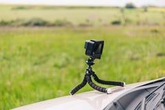 Appareil-photo d'action sur le trépied flexible sur le capot de la temps-faute d'enregistrement de voiture image stock