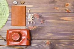 Appareil-photo dans un cas, un passeport et des coquillages sur un fond en bois Images libres de droits