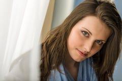 Appareil-photo de regard de brunette de jeune femme derrière le rideau photographie stock libre de droits