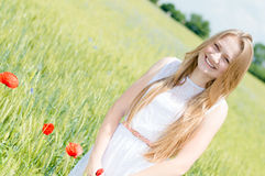 Appareil-photo de sourire de jeune belle femme et de regard heureux marchant dans le domaine de blé vert le jour d'été Photo libre de droits