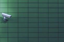 Appareil-photo de surveillance de surveillance contre un mur vert Images libres de droits