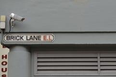 Appareil-photo de télévision en circuit fermé de plaque de rue de ruelle de brique Photographie stock libre de droits