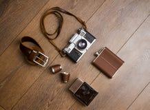 Appareil-photo de vintage et ceinture en cuir sur le plancher en bois Images stock