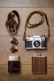 Appareil-photo de vintage et ceinture en cuir sur le plancher en bois Photographie stock libre de droits