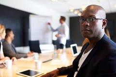 Appareil-photo exécutif masculin noir de revêtement avec l'expression sérieuse photo libre de droits