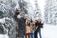 Appareil-photo futé de téléphone de prise d'homme prenant à amis de photo de Selfie la neige Forest Young People Group Outdoor de Photo stock