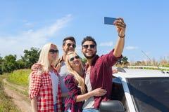Appareil-photo futé de téléphone de prise d'homme prenant à amis de photo de selfie la voiture de campagne de sourire Photos stock