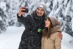Appareil-photo futé de téléphone de prise d'homme prenant à photo de Selfie la jeune neige romantique Forest Outdoor de sourire d Photo libre de droits