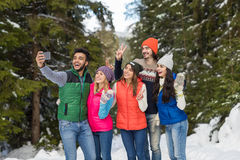 Appareil-photo futé de téléphone de prise d'homme prenant l'hiver de Forest Young People Group Outdoor de neige de photo de Selfi Photos stock