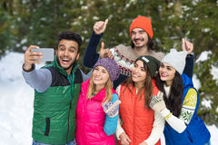 Appareil-photo futé de téléphone de prise d'homme prenant l'hiver de Forest Young People Group Outdoor de neige de photo de Selfi Photos libres de droits