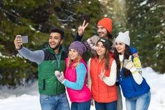Appareil-photo futé de téléphone de prise d'homme prenant l'hiver de Forest Young People Group Outdoor de neige de photo de Selfi Image stock
