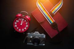 Appareil-photo, horloge, livre, sur la table en bois Image stock