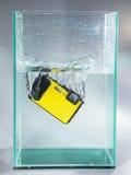 appareil-photo laissé tomber dans l'eau de récipient Image libre de droits