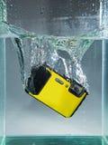 appareil-photo laissé tomber dans l'eau de récipient avec l'éclaboussure Photo stock