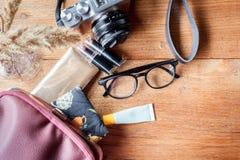 Appareil-photo, monocle, poudre, rouge à lèvres et sac Photographie stock