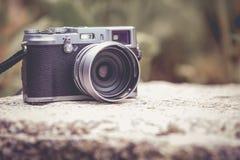 appareil photo numérique de style du vintage sur le rocher au-dessus du dos brouillé de nature image stock