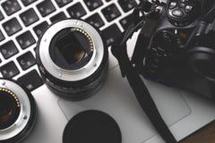 Appareil photo numérique, lentille et ordinateur portable concept du poste de travail de photographe Images stock