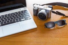 Appareil photo numérique, ordinateur portable, et lunettes de soleil sur la table en bois Photos stock