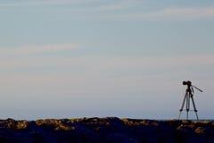 Appareil photo numérique sur un trépied avec des cieux de coucher du soleil Photographie stock libre de droits