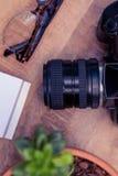 Appareil-photo par des verres d'oeil sur la table en bois Images libres de droits