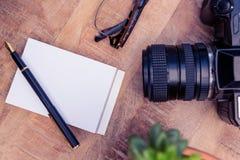 Appareil-photo par le stylo et papier sur la table en bois Photographie stock